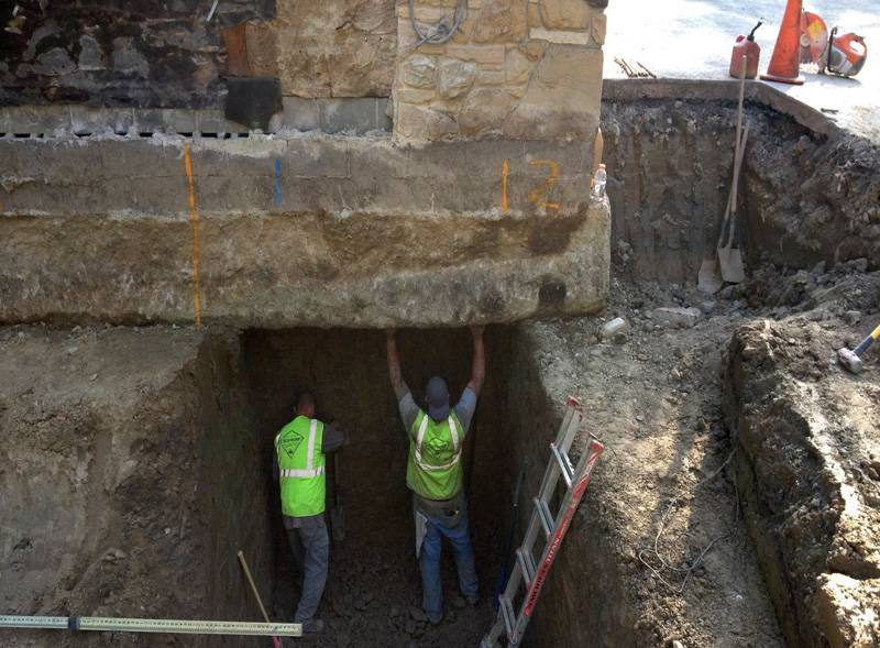two Sitework Developing crew members stand beneath corner of building foundation repairing it