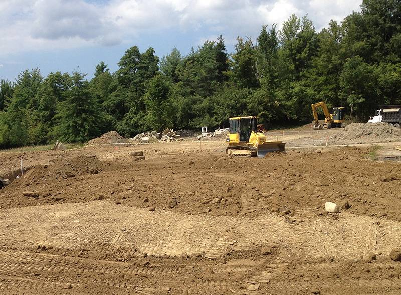 Sitework Developing crew uses small bob cat bulldozer to grade clear field near Cleveland Ohio