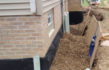 corner ground edge of home shows gravel and drainage pipes portion of residential waterproofing system by Sitework Developing Inc in Chagrin Falls Ohio