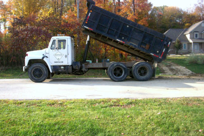 Sitework Developing Dump truck dumps dirt Solon Ohio home for residential waterproofing project