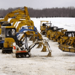 Sitework Developing near Cleveland displays fleet of diggers, dozers, and Bobcats lined up in the snow